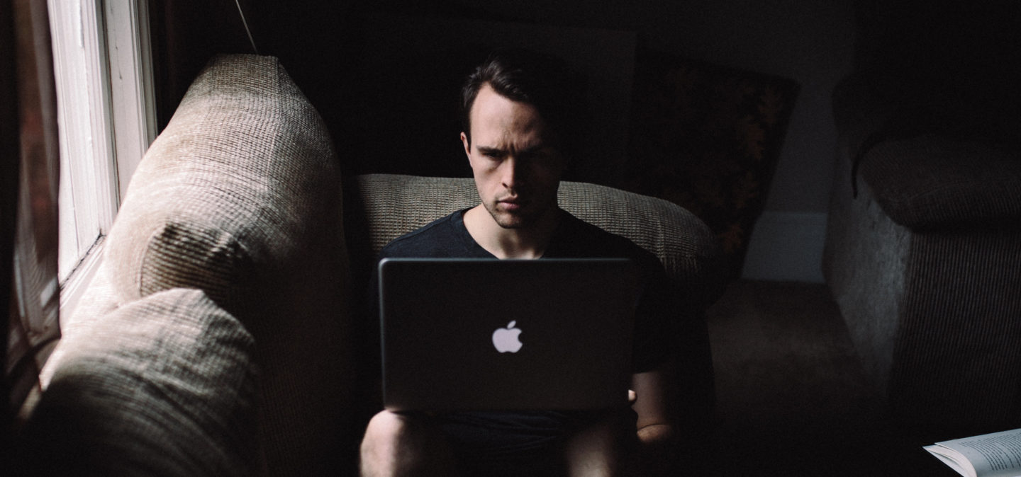 Dimly lit man sitting on couch with laptop on knees